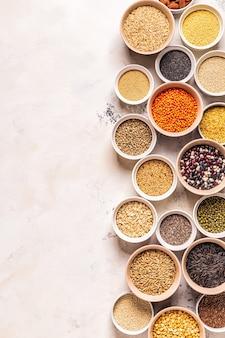 Conjunto de diferentes superalimentos: cereales integrales, frijoles y legumbres, semillas y frutos secos, vista superior.