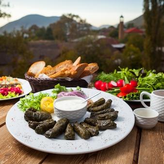 Conjunto de diferentes tipos de ensaladas y hojas de parra rellenas en una mesa con el pueblo en el fondo. vista de ángulo alto.