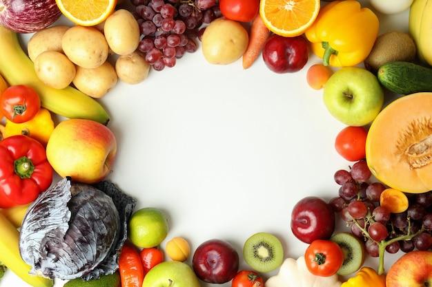 Conjunto de diferentes verduras y frutas sobre fondo blanco.