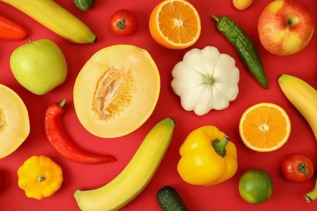 Conjunto de diferentes verduras y frutas sobre fondo rojo.