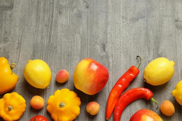 Conjunto de diferentes verduras y frutas sobre fondo de textura gris
