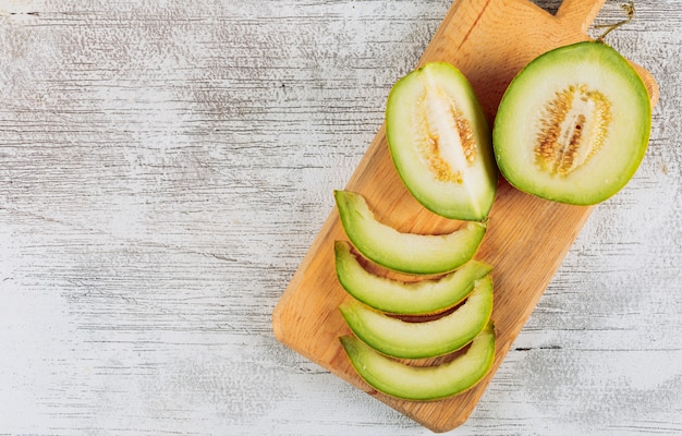 Conjunto de dividido en medio melón en tabla de cortar y rodajas de melón sobre un fondo de piedra blanca. vista superior. espacio para texto