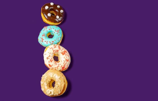 Conjunto de donuts surtidos con glaseado azul, espolvorear, migas de almendras, chocolate y malvaviscos primer plano aislado en un fondo morado. concepto de comida dulce (postre).