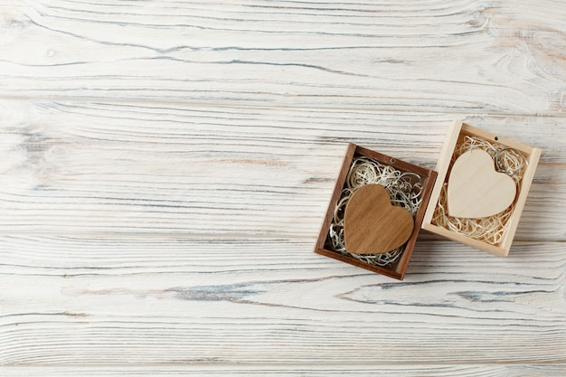Un conjunto de dos corazones de madera decorativos fondo de madera con espacio de copia. un regalo para el día de san valentín en una caja de madera de cerca. concepto de historia de amor