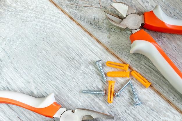 Conjunto de dos tipos diferentes de alicates, cuchillos laterales y sujetadores en un laminado gris. imagen sobre el tema de reparación, decoración, trabajos de construcción. copia espacio