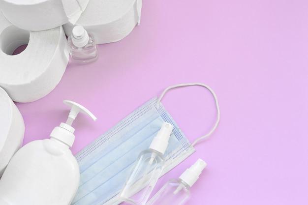 Conjunto de elementos importantes para los tiempos de cuarentena de covid-19. papel higiénico con mascarilla quirúrgica y desinfectante para manos con una botella de jabón líquido sobre fondo lila