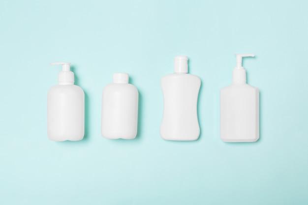 Conjunto de envases cosméticos blancos aislados en azul, vista superior con copyspace.