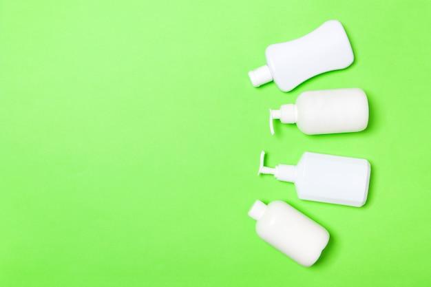 Conjunto de envases cosméticos blancos aislados en verde, vista superior con copyspace. grupo de envases de botellas de plástico para el cuidado corporal con espacio vacío
