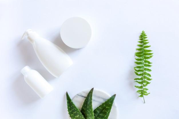 Conjunto de envases cosméticos, dispensador y hojas de aloe verde fresco sobre fondo blanco.