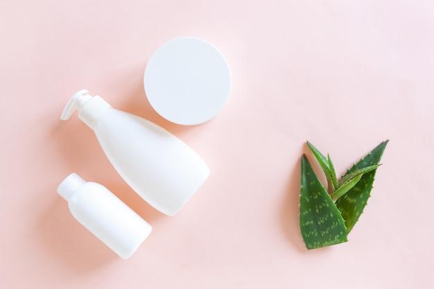 Conjunto de envases cosméticos, dispensador y hojas de aloe verde fresco sobre fondo rosa pastel.