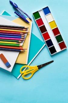Conjunto escolar de accesorios de cuadernos, brújulas, lápices, tijeras, pinturas y una goma de borrar sobre un fondo azul.