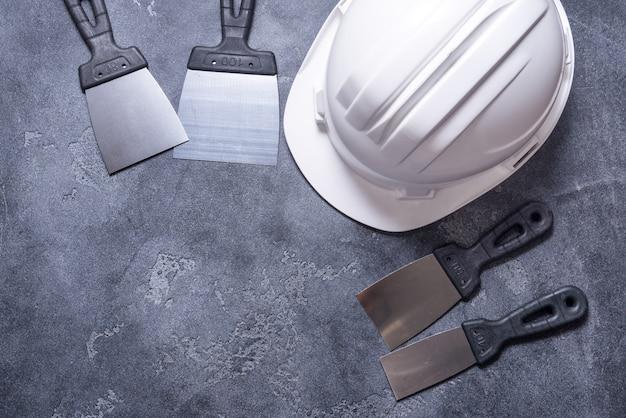 Conjunto de espátulas y casco sobre fondo gris