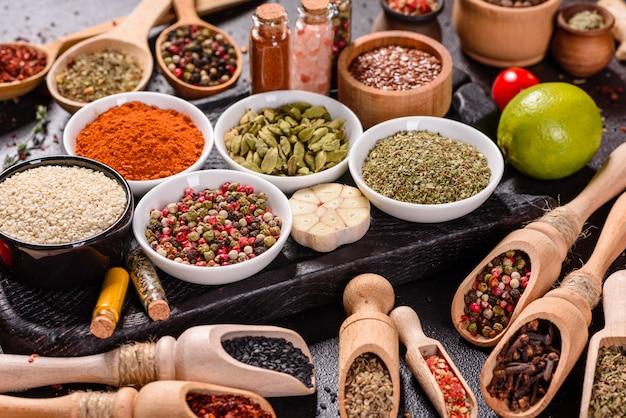 Un conjunto de especias y hierbas. cocina india. pimiento, sal, pimentón, albahaca. vista superior.