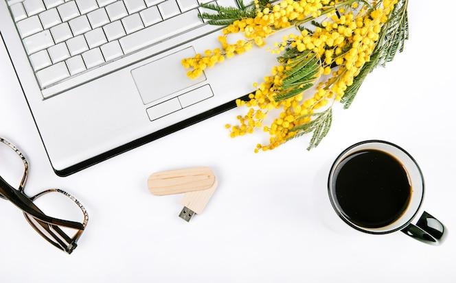 Conjunto festivo de primavera con flores y una computadora portátil sobre un fondo blanco