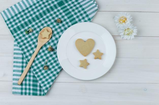 Conjunto de flores y galletas en plato y cuchara de madera sobre fondo de toalla de cocina y madera. endecha plana.