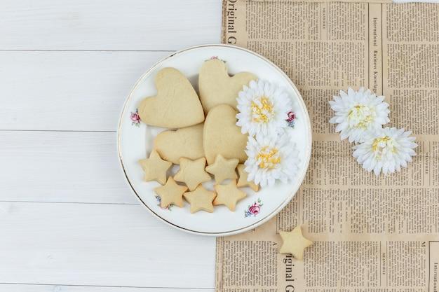 Conjunto de flores y galletas en un plato sobre fondo de madera y periódico. endecha plana.