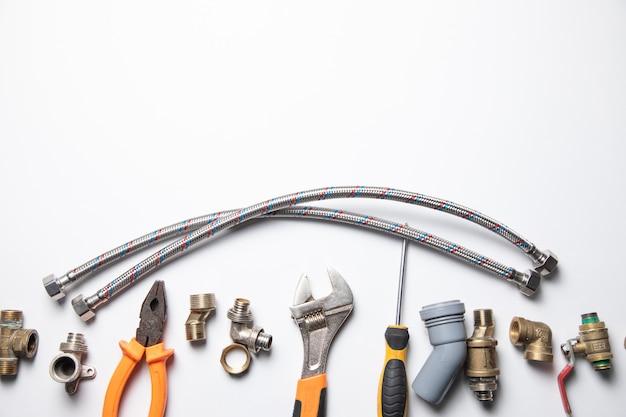 Conjunto de fontanería y herramientas en el blanco
