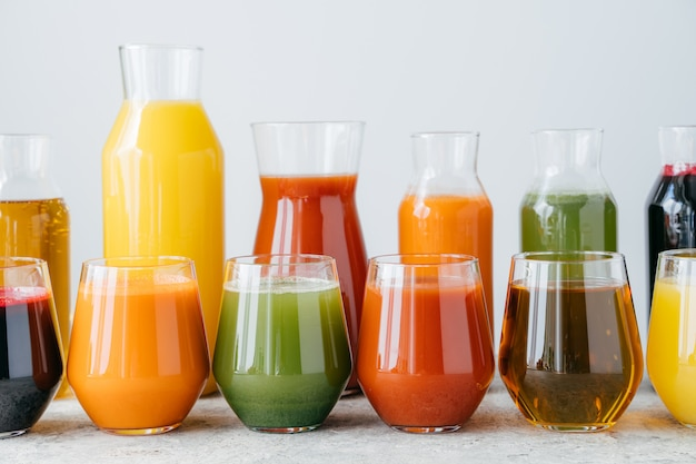 Conjunto de frascos de vidrio con bebidas multicolores de pie en fila.