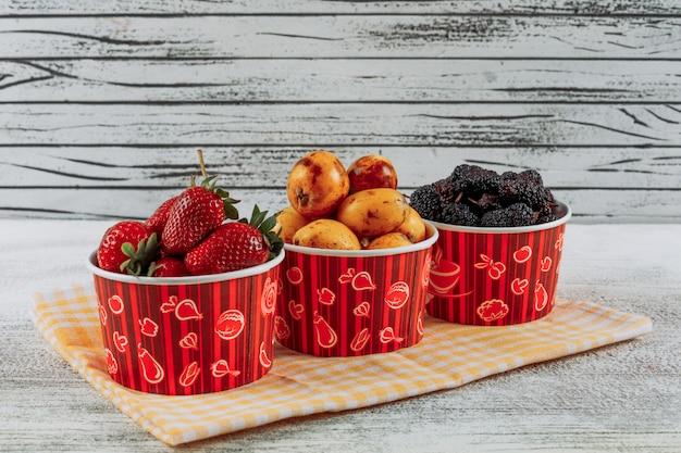 Conjunto de fresas, nísperos y moras en cuencos sobre un paño y fondo de madera clara. vista lateral.
