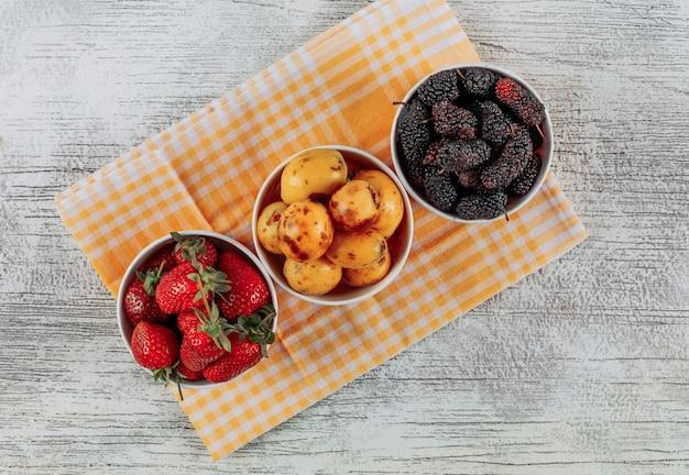 Conjunto de fresas, nísperos y moras en cuencos sobre un paño y fondo de madera clara. vista superior.