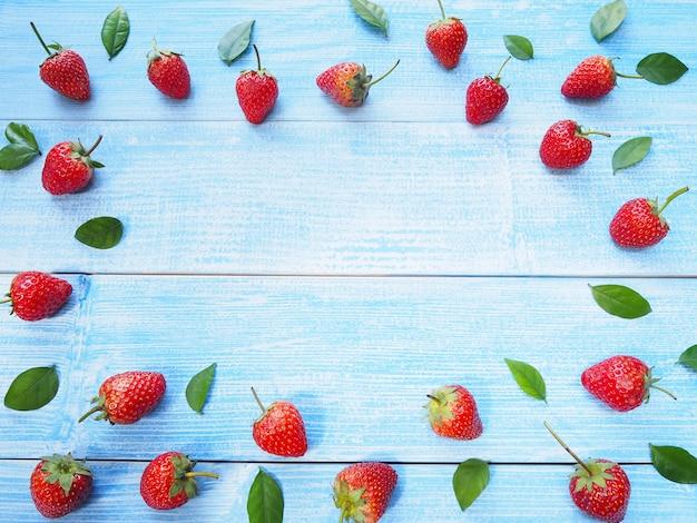 Conjunto de fresas rojas y hojas verdes sobre fondo de madera azul con espacio de copia. fruta jugosa.