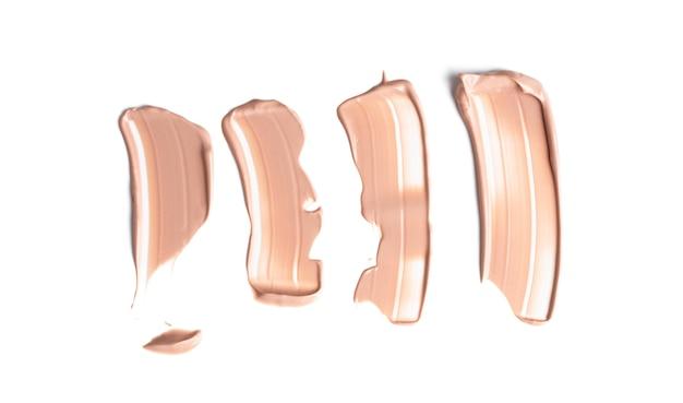 Conjunto de frotis suavemente beige de base cremosa de maquillaje aislado sobre fondo blanco. corrector cosmético. textura realista crema marrón para maquillaje.