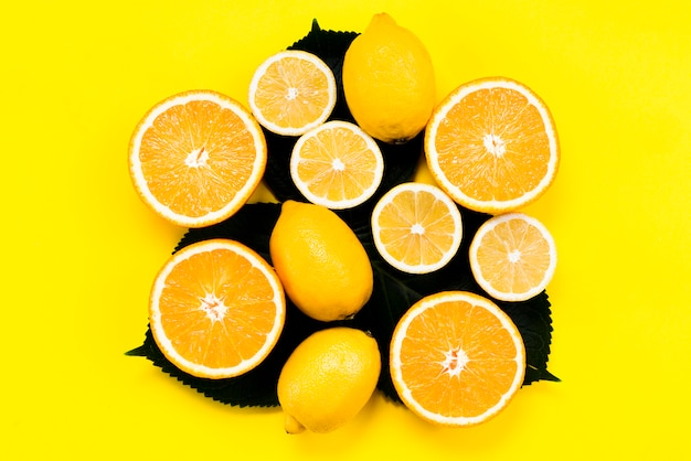 Conjunto de frutas cítricas en hojas sobre fondo amarillo
