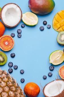 Conjunto de frutas tropicales kivi, naranja sanguina, coco, mango, arándano, lima, kiv sobre fondo azul. marco de alimentos frutas tropicales. flatlay con copyspace. concepto de inmunidad