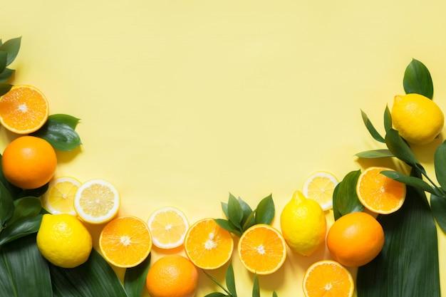 Conjunto de frutas tropicales, limón, naranja y hojas verdes sobre amarillo.