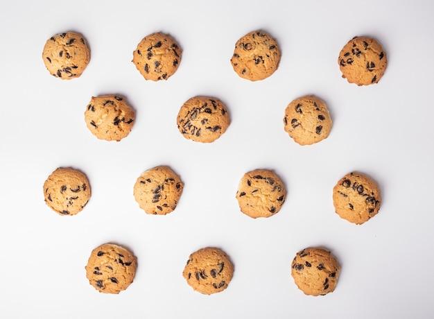 Conjunto de galletas con trozos de chocolate colocados simétricamente sobre fondo blanco