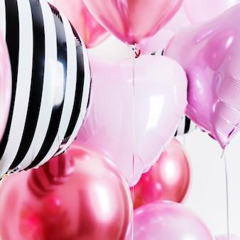 Conjunto de globos en forma de corazón y redondo rosa y rayas sobre fondo claro con espacio de copia.
