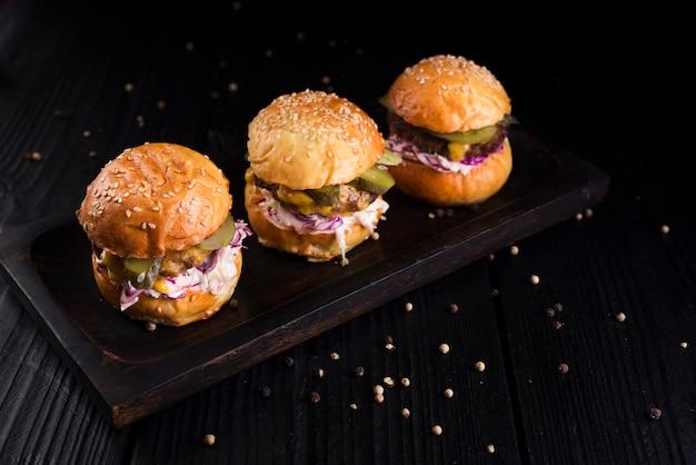 Conjunto de hamburguesas de alto ángulo sobre una tabla de madera