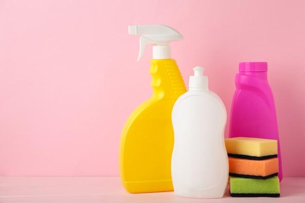 Conjunto de herramientas de limpieza en una mesa rosa con espacio de copia.