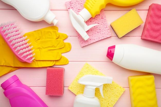 Conjunto de herramientas de limpieza en una pared rosa. vista superior