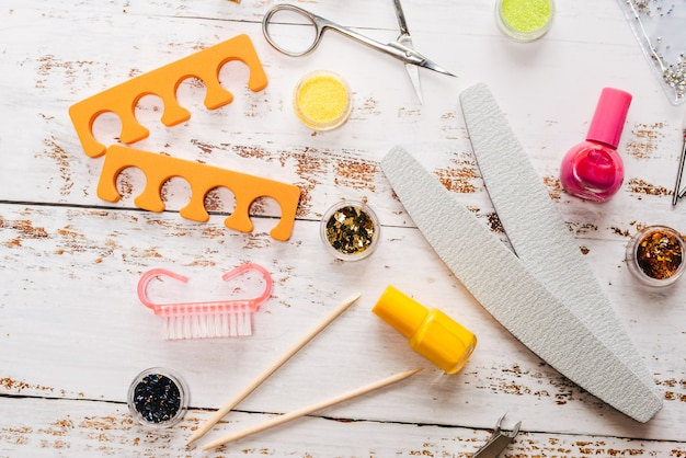 Conjunto de herramientas de manicura y esmaltes de uñas en madera blanca