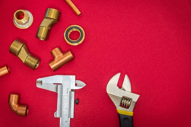 Conjunto de herramientas y repuestos para fontanería sobre fondo rojo.
