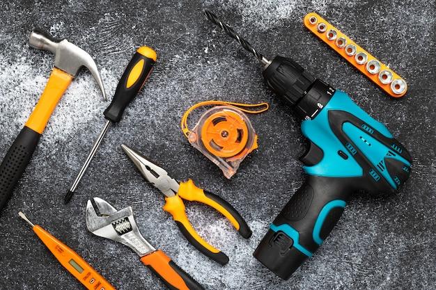 Conjunto de herramientas sobre una superficie oscura. concepto de renovación, tareas domésticas. composición laica plana. taladro eléctrico, destornillador, cinta métrica, llave inglesa, cuchillo y martillo para clavos en un escritorio negro.
