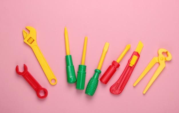 Conjunto de herramientas de trabajo de juguete para niños en rosa pastel.