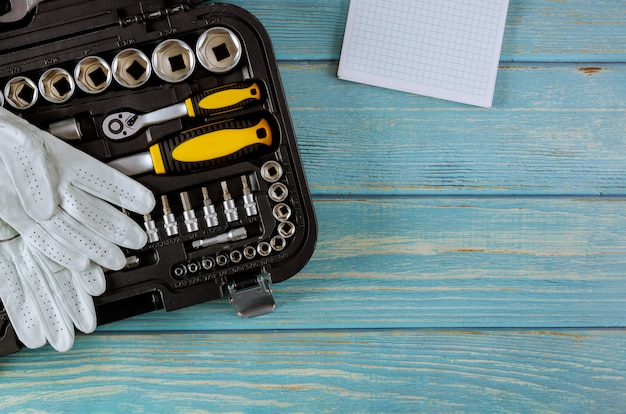 Un conjunto de hexágonos de diferentes tamaños con una llave fija de una caja de herramientas en un guante de trabajo protector