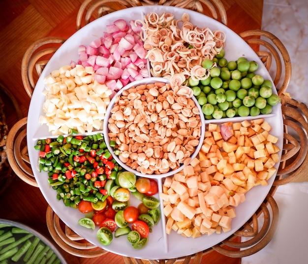 El conjunto de hierbas y especias y la rebanada vegetal en la bandeja para los ingredientes prueban el alimento picante del cocinero sabroso de asia