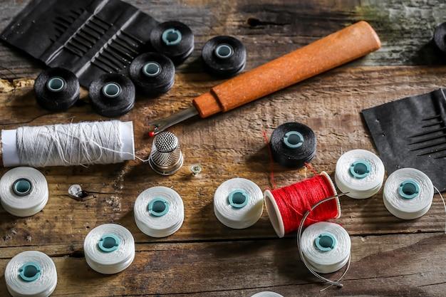 Conjunto de hilos de coser y accesorios en la pared de madera