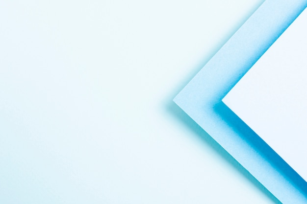 Conjunto de hojas de papel triangular en tonos azules con espacio de copia