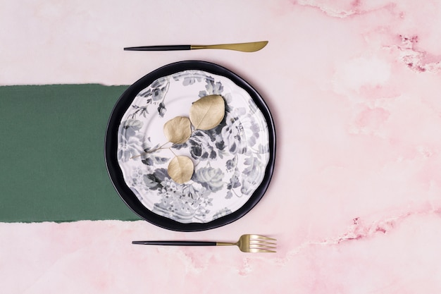 Conjunto de hojas secas en un plato cerca de papel y cubiertos