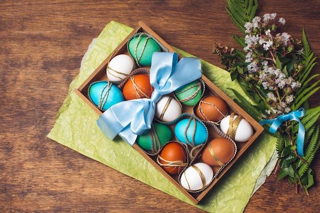Conjunto de huevos brillantes en caja en papel artesanal cerca de manojo de plantas