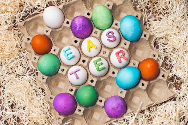 Conjunto de huevos brillantes en contenedor con título de pascua entre oropel