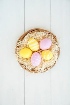 Conjunto de huevos brillantes en nido decorativo.