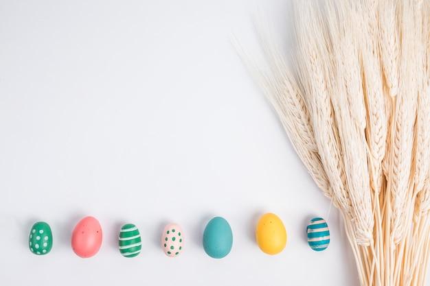 Conjunto de huevos de pascua brillantes cerca de manojo de trigo
