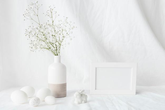 Conjunto de huevos de pascua cerca de la rama de una planta verde en florero, conejo decorativo y marco de fotos