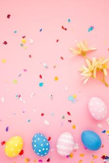Conjunto de huevos de pascua entre confeti brillante