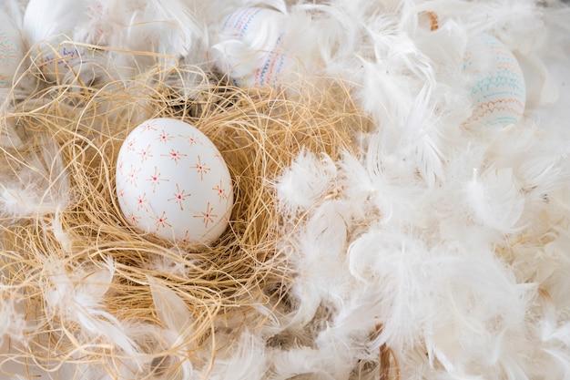 Conjunto de huevos de pascua en heno entre montón de plumas